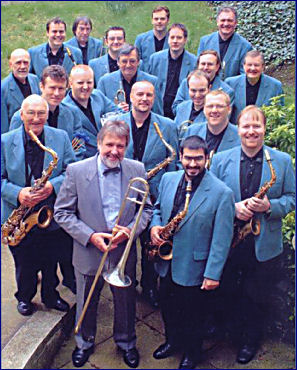 Jiggs Whigham and the BBC Big Band, viewed from above. Jiggs is wearing a suit and holding his trombone. The BBC Big Band are wearing pale blue jackets and dark shirts and holding their instruments.